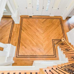 ニューヨークの中くらいの木のトラディショナルスタイルのおしゃれなかね折れ階段 (フローリングの蹴込み板、混合材の手すり) の写真
