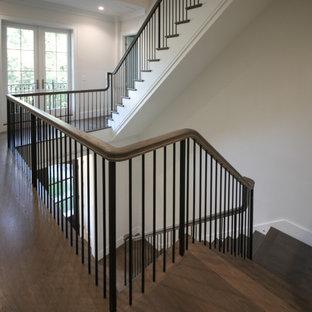 ワシントンD.C.の広い木のトランジショナルスタイルのおしゃれなかね折れ階段 (フローリングの蹴込み板、金属の手すり、パネル壁) の写真