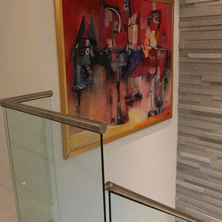 Ejemplo de escalera recta, tradicional renovada, con escalones de vidrio y contrahuellas con baldosas y/o azulejos