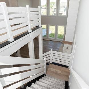 Ejemplo de escalera campestre con escalones enmoquetados, contrahuellas enmoquetadas y barandilla de madera