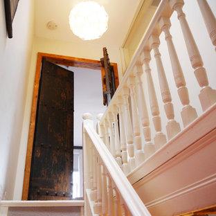 Esempio di una piccola scala a rampa dritta vittoriana con pedata in moquette e alzata in legno verniciato