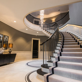 Inspiration for an expansive classic carpeted curved metal railing staircase in Belfast with wood risers.