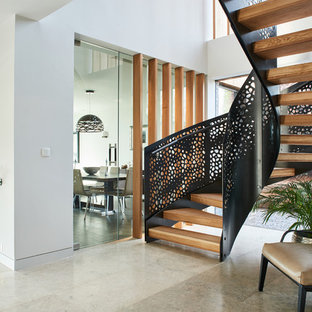 Photo of a contemporary wood spiral metal railing staircase in Devon with open risers.