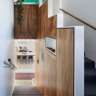 """Immagine di una piccola scala a """"U"""" minimal con pedata in moquette, alzata in moquette e parapetto in legno"""