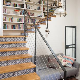 Ejemplo de escalera en L, urbana, con escalones de madera, contrahuellas con baldosas y/o azulejos y barandilla de cable