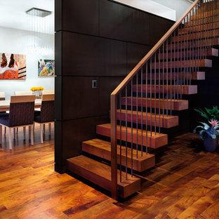 Ejemplo de escalera suspendida, actual, grande, sin contrahuella, con escalones de madera y barandilla de varios materiales