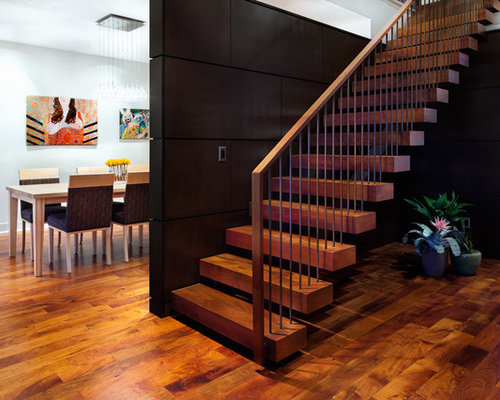 Large trendy wooden floating metal railing staircase photo in Austin