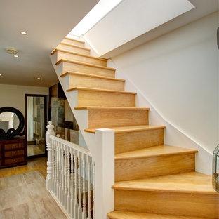 Foto de escalera curva, contemporánea, con escalones de madera y contrahuellas de madera