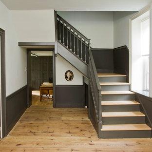 Diseño de escalera en L, de estilo de casa de campo, extra grande, con escalones de madera y contrahuellas de madera
