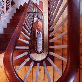 ボストンの中くらいの木のエクレクティックスタイルのおしゃれなサーキュラー階段 (木の蹴込み板、木材の手すり) の写真