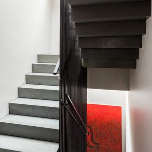 """Immagine di una grande scala a """"U"""" contemporanea con pedata in cemento, alzata in cemento e parapetto in metallo"""