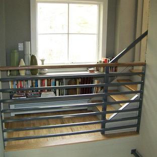Modelo de escalera recta, de estilo americano, pequeña, con escalones de madera, contrahuellas de madera pintada y barandilla de metal