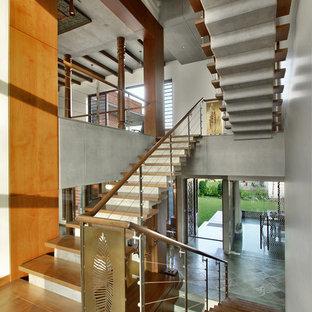 Стильный дизайн: п-образная лестница в восточном стиле с деревянными ступенями, бетонными подступенками и перилами из тросов - последний тренд