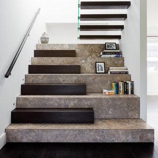 Imagen de escalera en U, actual, grande, con escalones de piedra caliza, contrahuellas de madera y barandilla de madera