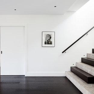 Modelo de escalera en U, contemporánea, grande, con escalones de piedra caliza, contrahuellas de madera y barandilla de madera