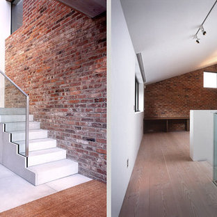 Example of a large minimalist concrete curved metal railing staircase design in Hertfordshire with glass risers