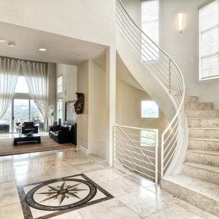 Diseño de escalera curva, minimalista, de tamaño medio, con escalones de piedra caliza, contrahuellas de piedra caliza y barandilla de metal
