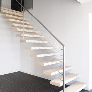 Modelo de escalera suspendida, actual, de tamaño medio, sin contrahuella, con barandilla de cable y escalones de madera