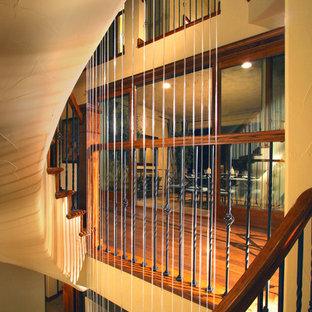 Foto di una grande scala curva rustica con pedata in moquette e alzata in moquette