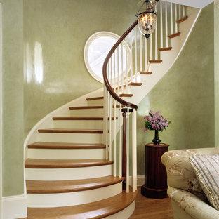 Immagine di una scala curva classica con pedata in legno e alzata in legno verniciato