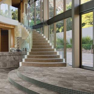 Modelo de escalera curva, mediterránea, con contrahuellas con baldosas y/o azulejos y barandilla de vidrio