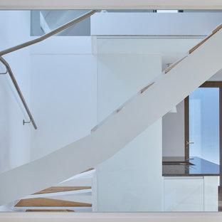 Modelo de escalera curva, minimalista, pequeña, con escalones de madera, contrahuellas de vidrio y barandilla de vidrio