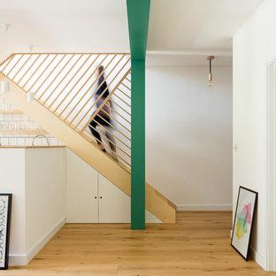 Ispirazione per una scala a rampa dritta scandinava di medie dimensioni con parapetto in legno