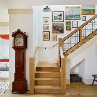 Cette photo montre un grand escalier nature en L avec des marches en bois, des contremarches en bois, un garde-corps en métal et du lambris de bois.