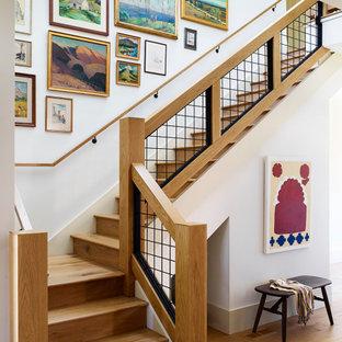 Inspiration för stora klassiska l-trappor i trä, med sättsteg i trä och räcke i metall