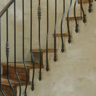 Imagen de escalera de caracol, rústica, grande, con escalones de madera, contrahuellas de madera y barandilla de metal