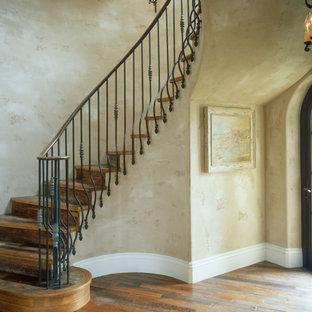 Foto di una grande scala a chiocciola stile rurale con pedata in legno, alzata in legno e parapetto in metallo