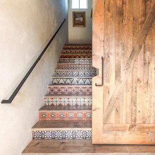 Ejemplo de escalera en L, campestre, grande, con escalones de madera, contrahuellas con baldosas y/o azulejos y barandilla de metal