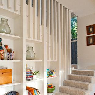 Imagen de escalera en U, actual, con escalones de madera pintada y contrahuellas de madera pintada