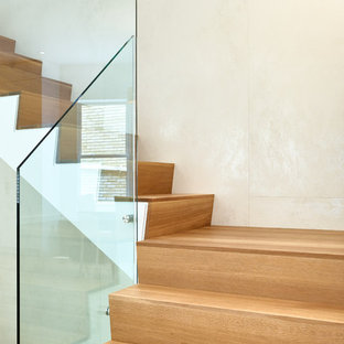 Example of a mid-sized wooden l-shaped glass railing staircase design in Toronto with glass risers