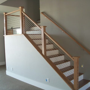 """Foto di una scala a """"L"""" moderna di medie dimensioni con pedata in legno, alzata in legno verniciato e parapetto in cavi"""