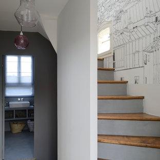 Foto di una scala curva minimal di medie dimensioni con alzata in cemento e pedata in legno