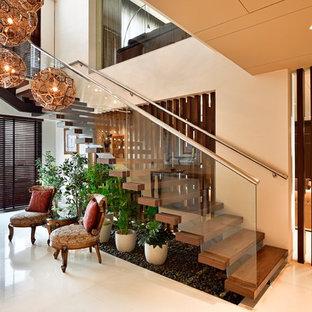 デリーの木のコンテンポラリースタイルのおしゃれなかね折れ階段 (ガラスの蹴込み板、金属の手すり) の写真