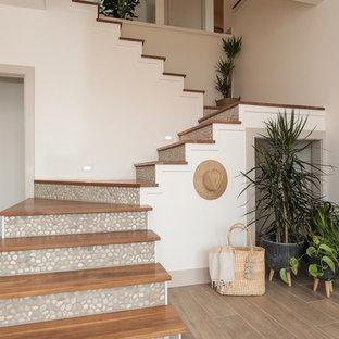Foto de escalera en L, marinera, con escalones de madera y contrahuellas con baldosas y/o azulejos
