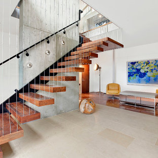 Example of a minimalist wooden floating open and cable railing staircase design in Portland