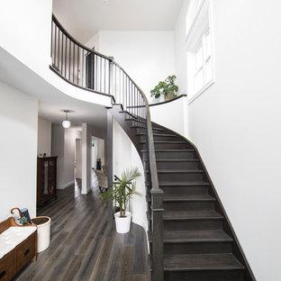Diseño de escalera curva, clásica, grande, con escalones de madera, contrahuellas de madera y barandilla de madera