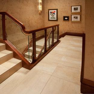 フェニックスのライムストーンのコンテンポラリースタイルのおしゃれな折り返し階段 (ライムストーンの蹴込み板、ガラスの手すり) の写真
