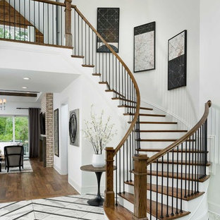 Example of a transitional wooden curved mixed material railing staircase design in Charlotte with painted risers
