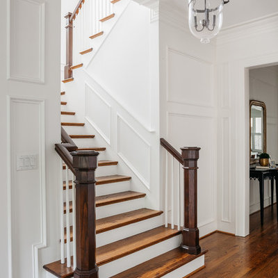 Elegant wooden u-shaped staircase photo in Houston with painted risers