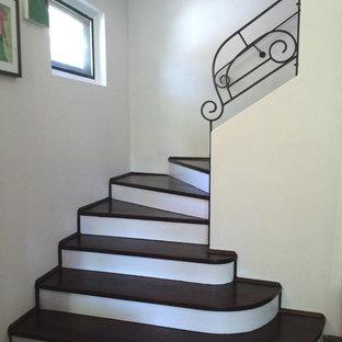 Diseño de escalera curva, minimalista, de tamaño medio, con escalones de madera y contrahuellas de madera pintada