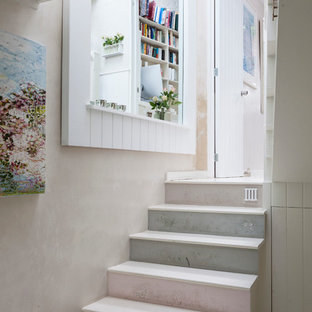 Example of a cottage chic painted straight staircase design in London with painted risers