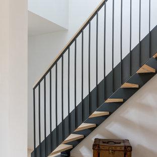 Aménagement d'un escalier sans contremarche droit scandinave de taille moyenne avec des marches en bois et un garde-corps en métal.