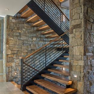На фото: лестница на больцах в современном стиле с деревянными ступенями и перилами из тросов без подступенок с