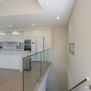 Modelo de escalera en L, industrial, de tamaño medio, con escalones con baldosas, contrahuellas con baldosas y/o azulejos y barandilla de vidrio