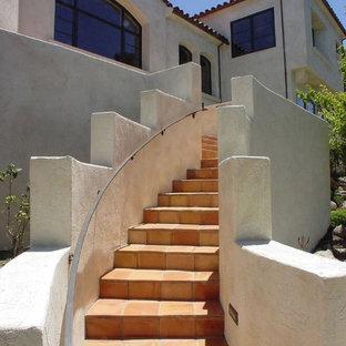 Foto de escalera mediterránea con escalones de terracota, contrahuellas de terracota y barandilla de metal