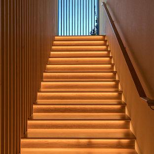 Exemple d'un grand escalier droit tendance avec des marches en bois, un garde-corps en bois et des contremarches en bois.